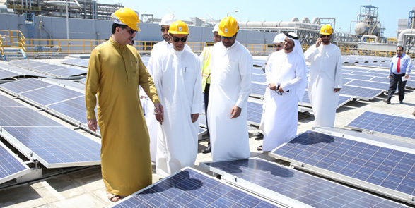 Officials inspect a rooftop system at the site of a new power and desalination plant in the city. Source: DEWA.